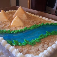 Egyptian Pyramids Made for a girl who loves all things Egyptian. Pyramids are mad of fondant and brushed with gold dust. Water is piping gel tinted blue....