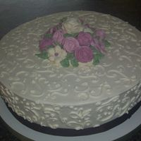 100_1337.jpg Vanilla Buttercream frosting with buttercream flowers in shades of pink. Chocolate brown accent ribbon