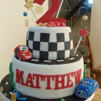 Pixar's Cars Cake Vanilla cake, strawberry filling, mmf fondant. Cars are made of styrofoam and mmf fondant. Thanks for looking! :)
