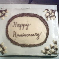 Anniversary White cake with buttercream frosting, yellow BC flowers, brown leaves and stems