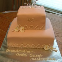 Grandma's 90Th Birthday Bottom is butter pecan, top is lemon. Covered in fondant with gum paste flowers.