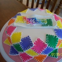 Jeannettes Birthday Cake Make this cake for my sisters birthday. Is white cake, cream filling. Outside is fondant squares with royal icing stitches. Birthday plaque...