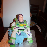 Buzz Birthday  this is a 10 inch buzz in rice crispies treat and gum paste sit on a fondant blanket on a 9inch chocolat cake. I madi it for the 3 years...