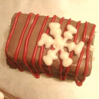 Chocomini Miniature chocolate cake covered in chocolate buttercream and drizzled with red chocolate.Snowflake is made with white chocolate