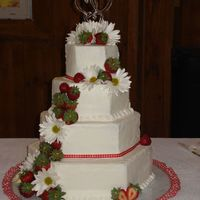 Strawberries And Daisies 4 tier-hexagon , white cake with buttercream icing. Decorated with strawberries, daisies, and gingham ribbon.