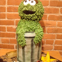 Oscar The Grouch Chocolate & Vanilla Cakes with fudge filling. Decorated in fondant and buttercream. Garbage on the board made of gumpaste, modeling...