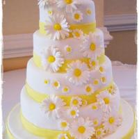 Fondant Covered Daisy Wedding Cake Fondant covered yellow cake with buttercream icing. The daisies were made out of gum paste and the ribbon is fondant.