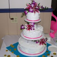 Round Hawaiian Themed Wedding Cake Tiered round cake with bright pink ribbon for a Hawaiian Themed wedding