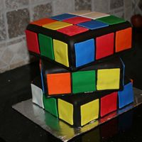 Rubix Cube Cake layers top to bottom; yellow, strawberry and white chocolate with white chocolate chips. Strawberry buttercream icing covered in dark...