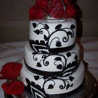 Black And Red Wedding The cake was a red velvet with cream cheese frosting, it covered in white fondant and the black decoration where all done by hand in black...