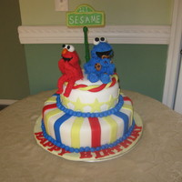 Laughing Elmo And Cookie Monster  1st elmo and cookie monster cake . 2 tier cake bottom tier is a yellow cake walmond buttercream, top tier is a red velvet cake w/cream...