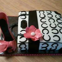 Purse/shoe vanilla cake with vanilla buttercream. covered in MMF. Gumpaste flower, and shoe.