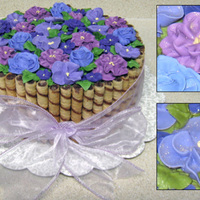 Purple Flowers For Mom's Birthday Sides are covered in chocolate hazelnut rolled wafer cookies cut to size. Flowers are royal icing covered in copious amounts of pearl dust...