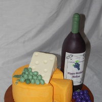 "Wine & Cheese Tray Wine bottle is RKT covered in fondant. ""Cheeses"" are frosted in buttercream, with fondant grapes. TFL!!"