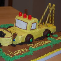 "Construction Truck Bottom layer is chocolate cake, with a ""path"" carved out for the truck, which is yellow cake."