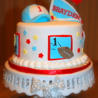"1St Birthday Cake - Boy 1st birthday cake - sports themed - 8"" round.Hat was formed with the mini-ball pan and rice krispie treats.Entire cake was done in..."