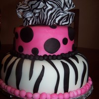 Sweet 16 Zebra Fondant covered cake. Zebra print on bottom layer and fuschia and black dots on top tier zebra print ribbon as topper