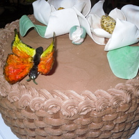 Magnolia Flower And Butterlfy classic buttercream cake with chocolate buttercream icing done in basket weave pattern. Flowers, leaves, and butterfly made from gum-paste...