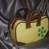Handbag Cake First attempt at a handbag cake. Second handle got broken hence the lopsided look. Please all feedback/comments welcomed.