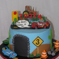 Lightening Mcqueen Birthday Cake This cake was made for a three year old that loves Lightening McQueen. I added details such as a rock slide on the road, a caution sign...