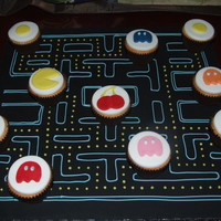 Pac Man Cupcakes Brief was retro games in cake so came up with this idea.Iced board and marked out game then using cupcakes made the Pac man, ghosts etc.