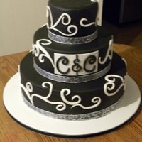 Black And White Swirls   This is a three tier wedding cake covered with vanilla flavored black fondant and white fondant swirls.