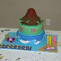 Hula Graduation Cake Vanilla cake, buttercream filling, and fondant topping. The volcano is rkt covered in fondant. The beach is brown sugar.