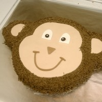Monkey Face White cake with BC and MMF accents. The face is 10in and the ears were cut with biscuit cutters out of an 8in cake. Iced the entire thing...