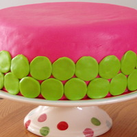 "Hot Pink And Lime Dots 10"" lemon cake with lemon curd filling. Topped with hot pink fondant and lime green dots around the edge."