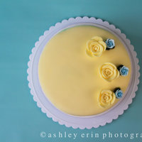Yellow Rose Cake cake covered in yellow fondant. decorated with yellow fondant roses and blue roses.