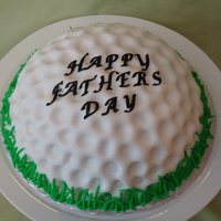 Golf Ball Fathers Day Cake  Cake baked with Wilton sports ball pan. White cake with buttercream icing and fondant icing. Rolled fondant just a tad thicker than normal...