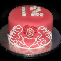 Pink Tiara   Cake covered in pink fondant with white fondant rosettes. Freehand royal icing tiara. Heart is made from dragees.