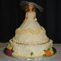 Bride In Ivory Wonder Mold doll atop a large petal-shaped cake. Ivory buttercream with royal flowers (in Fall colors).