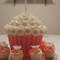 Giant Flower Cupcake White chocolate raspberry cake with white chocolate buttercream. Candy liner with fondant flowers.