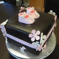 Baby Girl Cake Chocolate cake with caramel buttercream and chocolate ganache filling. Chocolate fondant covering with gum paste flowers and baby shoes....
