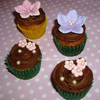 White Chocolate Baby Cup Cakes Mini white chocolate and Baileys liqueur cupcakes with a whipped chocolate ganache swirl. Gumpaste flowers and sugar pearls.