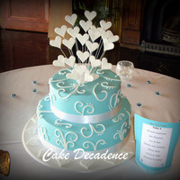 Teal Scroll & Hearts Wedding Cake 11 inch dark and white chocolate marble mudcake and an 8 inch cherry ripe mudcake, both layered and coated with dark chocolate ganache and...