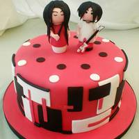 White Stripes Birthday Cake Design inspiration for the side decoration taken from a band photo. The little gumpaste Meg and Jack are in the style of Momiji dolls.
