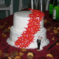 "My First Wedding Cake It was a yellow cake with buttercream frosting and royal icing poinsettias. The bride wanted something simple and ""Christmasy""."