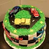 Race Track Cake yellow and chocolate checkerboard cake with black chocolate mmf and vanilla colored mmf, vanilla bc grass and matchbox car toppers. tfl