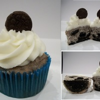 Oreo Cupcake white cake with oreo bits and a big oreo bottom and vanilla buttercream frosting.