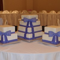 "Purple Bows Center cake is 4 tier stacked cake, 14"", 12"", 10"", 8"". Two smaller cakes are 10"" and 8"" dummy cakes. Fondant/..."