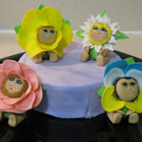 Spring Flower Babies Cake vanilla cake, vanilla frosting with purple marble fondant and figures are fondant flower babies (ann geddes style) each baby took about two...
