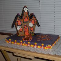 Trick Or Treat Wilton gingerbread kit on top of yellow cake colored orange and choc. BC.