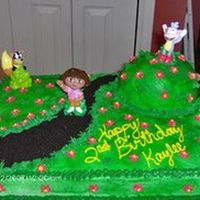 Dora Birthday Yellow cake with buttercream icing. I used crumbled Oreos for the path and the mom brought me the figurines.