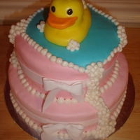 Bubbly Ducky 2-tier white cake with pink buttercream filling, fondant covering. Hand sculpted ducky and bubbles. Real ribbons.