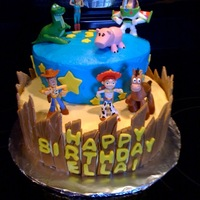 Toy Story Cake White cake with buttercream frosting, fondant accents and toy figurines.