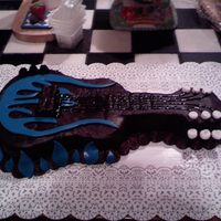Guitar With Blue Flames This is a devil's food cake with fudge icing. The flames are mmf. This was my very first time making and using mmf. This was also my...