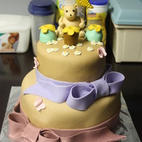 Winnie The Pooh Baby Shower Cake   2 tiered baby shower cake. Covered in MMF. Figures and ribbon are fondant.