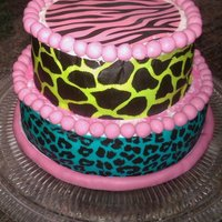 Colorful Zebra Print Red velvet cake w/ buttercream frosting. The borders are made of fondant. For the pattern around the cake I used Duff's edible cake...